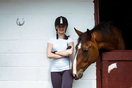reigns: Smiling jockey posing next to horse in the countryside