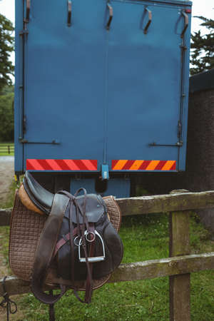 pursuits: Saddle laid on fence in the countryside