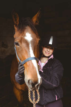 reigns: Female rider brushing her horse in the countryside LANG_EVOIMAGES