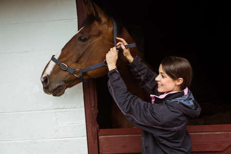 reigns: Female rider fixing saddle in the countryside