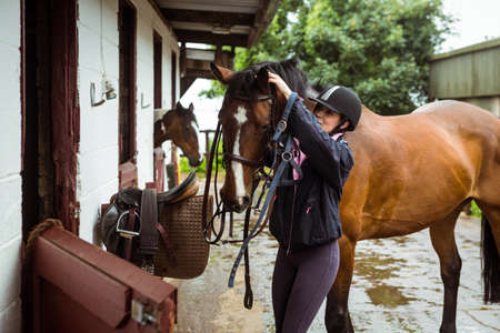 reigns: Female rider taking off reigns in the countryside  LANG_EVOIMAGES