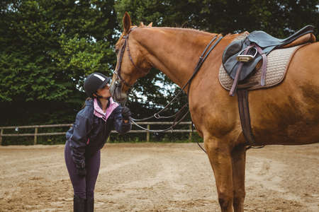 reigns: Female rider kissing her horse in the countryside LANG_EVOIMAGES