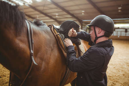 reigns: Female rider securing saddle in the countryside LANG_EVOIMAGES