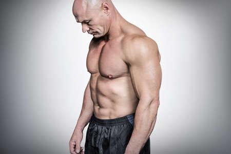 man looking down: Side view of sad bald man looking down against grey vignette LANG_EVOIMAGES