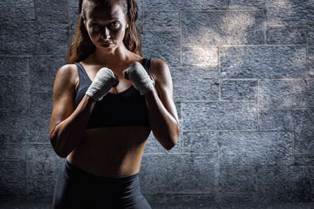 fighting stance: Portrait of female athlete with fighting stance against grey