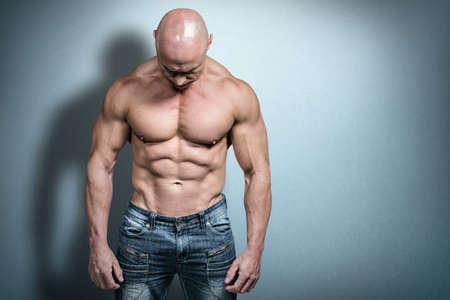 man looking down: Muscular sad man looking down against teal, blue