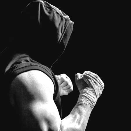 fighting stance: Muscular man in blue hood with fighting stance against black LANG_EVOIMAGES