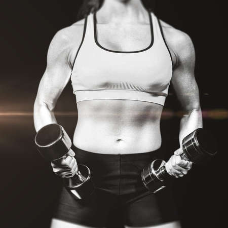free weight: Midsection of woman exercising with dumbbells against black