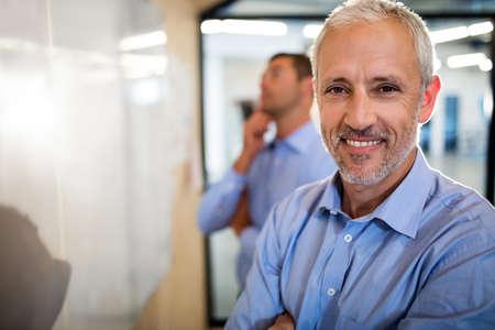 reuniones empresariales: Sonriente hombre de negocios con los brazos cruzados en la oficina