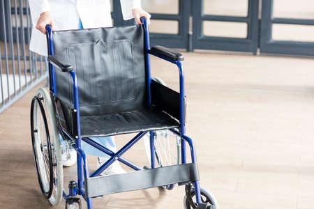 paraplegic: Doctor que muestra una silla de ruedas en el pasillo del hospital LANG_EVOIMAGES