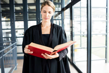 attentively: Female lawyer reading  a book attentively and walking LANG_EVOIMAGES