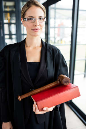 female lawyer: Female lawyer holding her book and her hammer in her firm LANG_EVOIMAGES