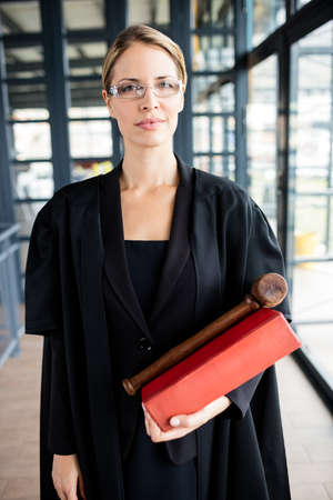 female lawyer: Female lawyer wears glasses and holding her book and her hammer