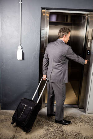 going in: Businessman going in the lift of his company
