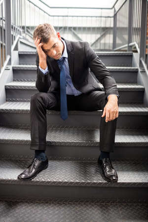 in low spirits: Portrait of a disappointed businessman sitting on stairs