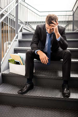 in low spirits: Portrait of a fired businessman sitting on stairs