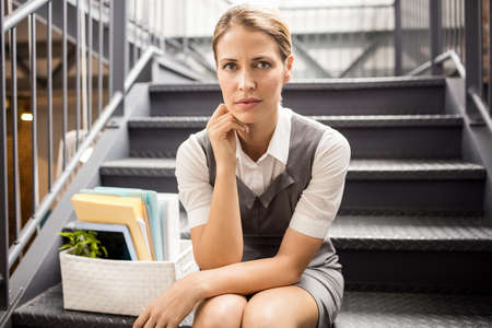in low spirits: Portrait of a fired businesswoman sitting on stairs LANG_EVOIMAGES