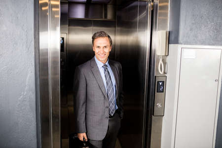 going out: Businessman going out the lift of his company
