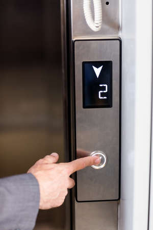 elevators: Close up view of businessman pressing elevators button in office