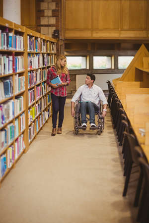 classmate: Student in wheelchair talking with classmate in library