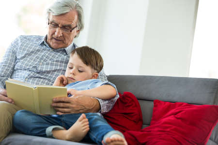 multi family house: Grandfather and grandson reading a book on couch in living room