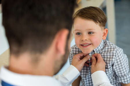 get ready: Father buttoning up son to get ready