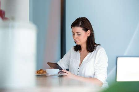 mujeres morenas: Mujer que usa la tableta con el café en la cocina LANG_EVOIMAGES