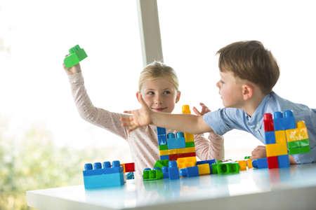 siblings: Cute siblings playing building blocks on the table
