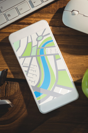 digitally generated image: Digitally generated image of map  against smartphone on desk Stock Photo