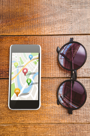 representations: Navigation pointers with various representations on map against view of glasses and a smartphone Stock Photo