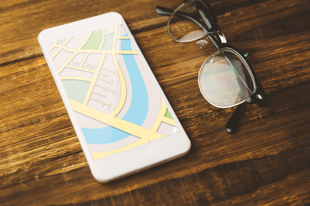 high angle view: Illustrative image of map  against high angle view of cellphone and eyeglasses Stock Photo