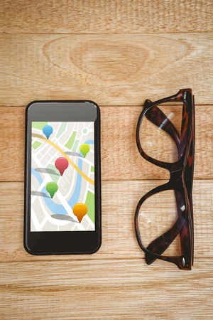 multi colored: Multi colored navigation pointers on map against view of glasses and a smartphone Stock Photo
