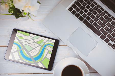 digitally generated image: Digitally generated image of map  against tablet on desk