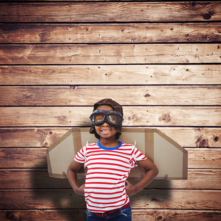 pretending: Smiling boy pretending to be pilot against wooden planks background