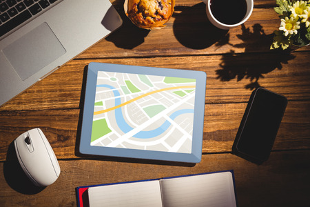 books on a wooden surface: Digital image of map  against view of a desk Stock Photo