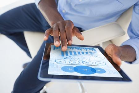 usando computadora: los datos de color azul contra el empresario que usa la tableta digital mientras que se sienta en la silla Foto de archivo