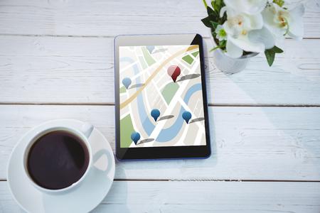 digitally generated image: Digitally generated image of navigation pointers  against tablet on desk