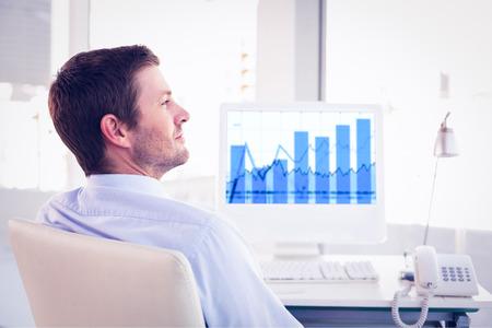 Smiling businessman sitting at his desk  against blue data