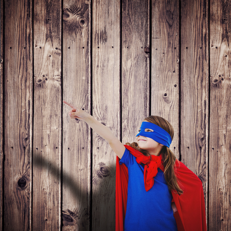 pretending: Masked girl pretending to be superhero against wooden planks background
