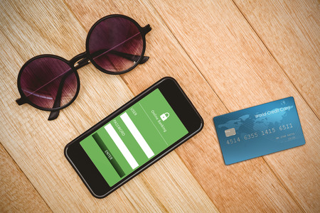 digitally generated image: Digitally generated image of world credit card against view of glasses and a smartphone