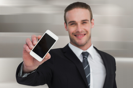 against abstract: Smiling businessman showing his smartphone screen against abstract white design Stock Photo