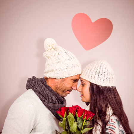 clear day in winter time: Smiling couple nose-to-nose holding roses bouquet against open door on white wall