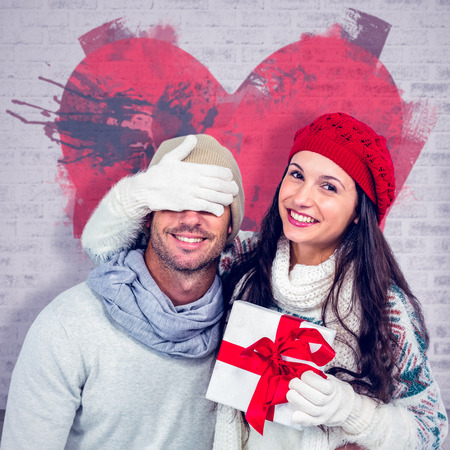 clear day in winter time: Smiling woman covering partners eyes and holding gift against open door on brick lined wall Stock Photo