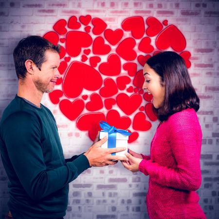 recibo: Emocionado novia tomando regalo del novio contra la pared de ladrillo gris