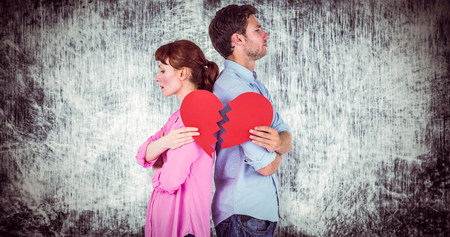 fighting styles: Couple holding a broken heart against grey background Stock Photo
