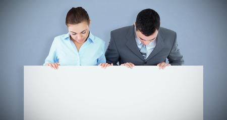 Socios comerciales que miran abajo firman que están sosteniendo contra fondo gris