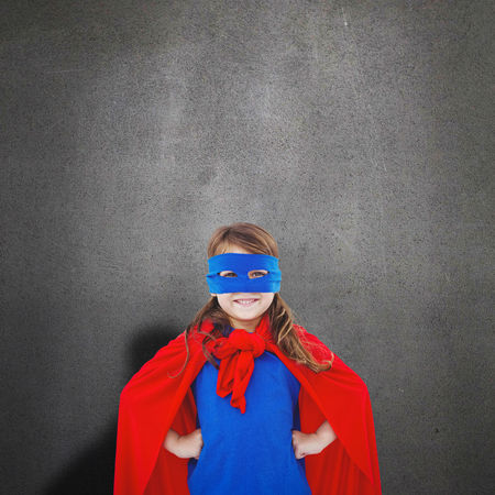 pretending: Masked girl pretending to be superhero against grey room