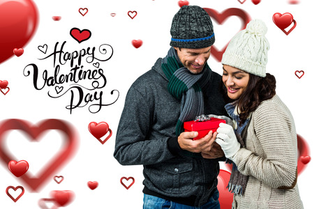exchanging: Festive couple exchanging a gift against happy valentines day Stock Photo