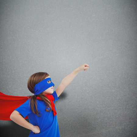 pretending: Masked girl pretending to be superhero against grey background