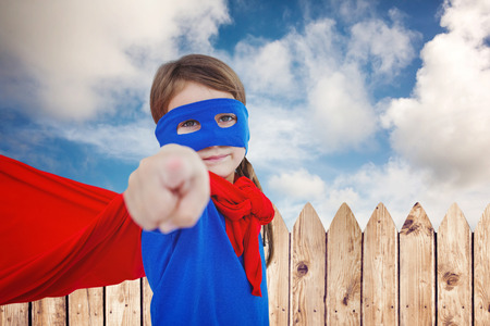 pretending: Masked girl pretending to be superhero against fence under blue sky